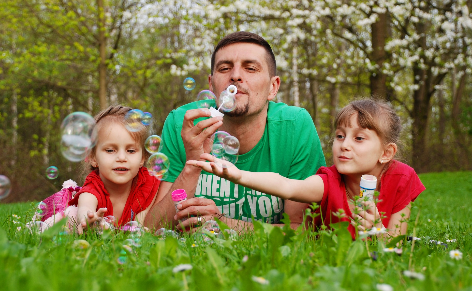 Dad blowing bubbles with daughter in spring